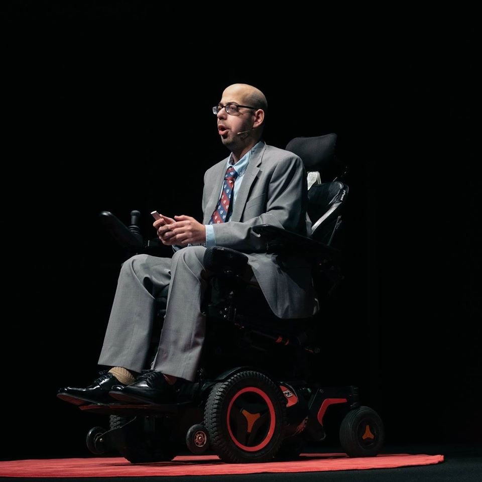 Photo of Mark Bookman, a young, white motorized wheelchair user. Mark is wearing a grey suit and is positioned against a black background on a red carpet.